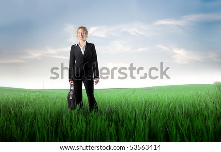 Smiling businesswoman on a green meadow
