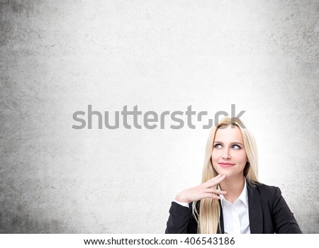 Smiling businesswoman on blank concrete wall background. Mock up - stock photo