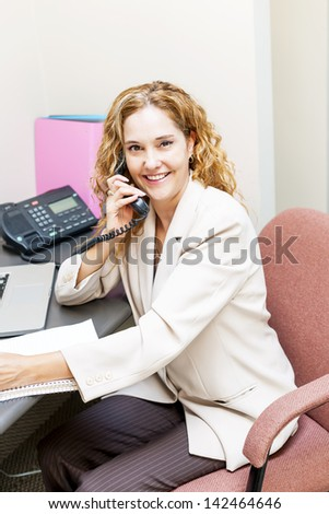 Smiling businesswoman on phone in office workstation - stock photo