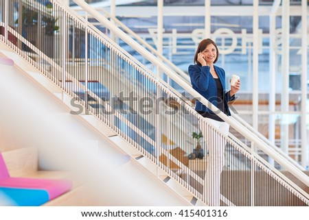 Smiling businesswoman on stairs in modern office with her phone - stock photo