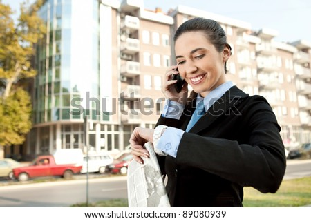 smiling businesswoman on the phone checking the time, concept-busy woman - stock photo