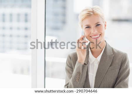 Smiling businesswoman on the phone looking at camera in an office - stock photo
