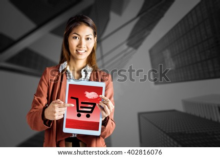 Smiling businesswoman pointing a tablet against skyscraper - stock photo