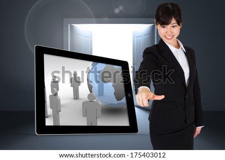 Smiling businesswoman pointing against doors opening revealing light - stock photo