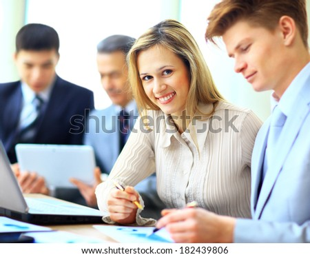 Smiling businesswoman posing while colleagues talking together in bright office - stock photo