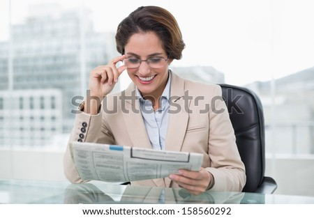 Smiling businesswoman reading newspaper at her desk in bright office - stock photo