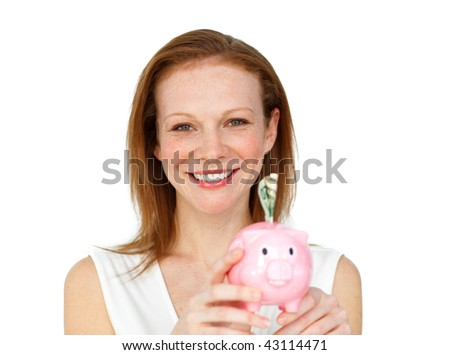 Smiling businesswoman saving money in a piggybank against a white background - stock photo