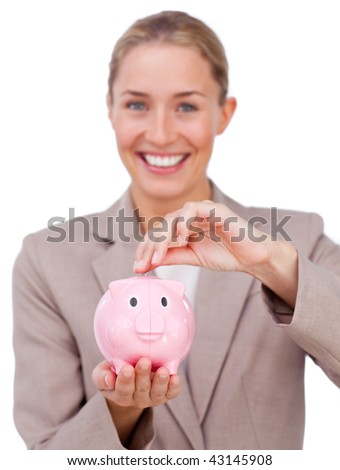 Smiling businesswoman saving money in a piggybank and looking at the camera against a white background - stock photo