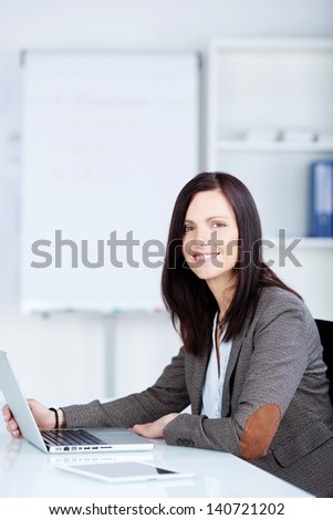 Smiling businesswoman sitting and working using her laptop