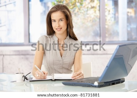 Smiling businesswoman sitting at desk in office, writing into personal organizer, looking at camera.? - stock photo