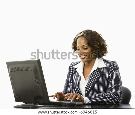 Smiling businesswoman sitting at desk typing on computer.
