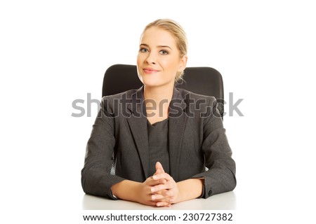 Smiling businesswoman sitting at the desk. - stock photo