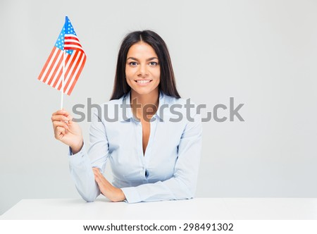 Smiling businesswoman sitting at the table with american flag isolated on a white background - stock photo