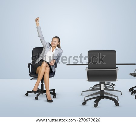 Smiling businesswoman sitting in chair and raising right hand. Business office, winner