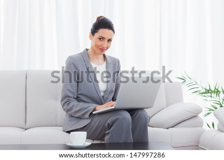 Smiling businesswoman sitting on sofa using laptop at office