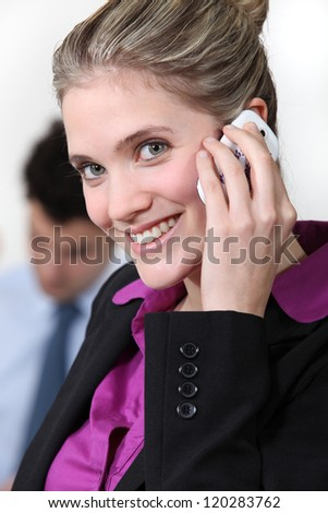 Smiling businesswoman taking on her mobile phone - stock photo