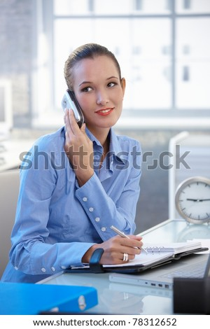 Smiling businesswoman talking on cellphone and writing into notebook at office desk.? - stock photo
