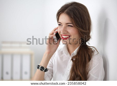 Smiling businesswoman talking on the phone at the office - stock photo