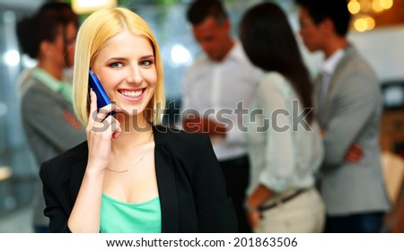 Smiling businesswoman talking on the smartphone in front of colleagues - stock photo