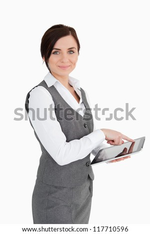Smiling businesswoman using a touchscreen tablet against white background - stock photo