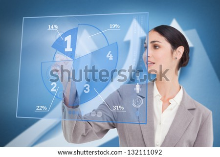 Smiling businesswoman using blue pie chart interface with arrows on background - stock photo