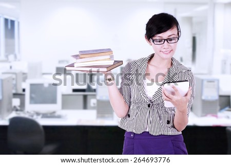 Smiling businesswoman using digital tablet with books on her hand at office - stock photo