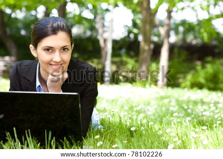 smiling businesswoman using laptop in nature - stock photo