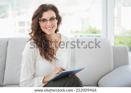 Smiling businesswoman using tablet on couch in the office - stock photo