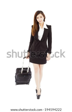 smiling businesswoman walking and carrying the baggage - stock photo