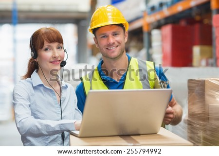 Smiling businesswoman wearing headset using laptop in warehouse - stock photo