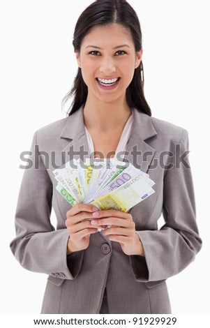 Smiling businesswoman with bank notes in her hands against a white background