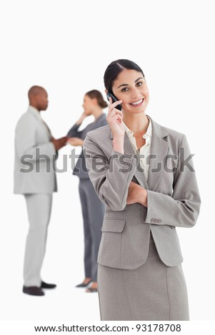 Smiling businesswoman with cellphone and colleagues behind her against a white background
