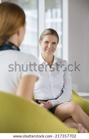 Smiling businesswoman with colleague at lobby - stock photo