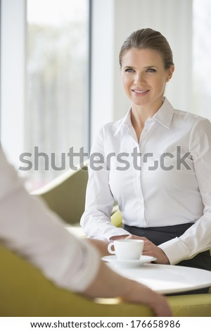Smiling businesswoman with colleague at office lobby - stock photo