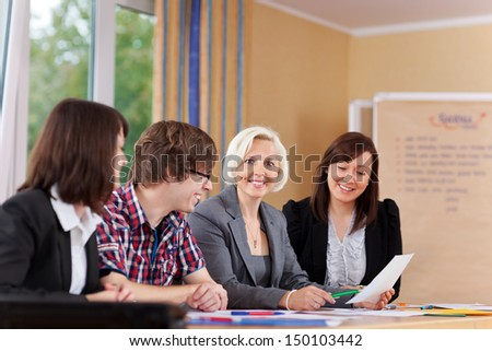 smiling businesswoman with colleagues in a meeting - stock photo