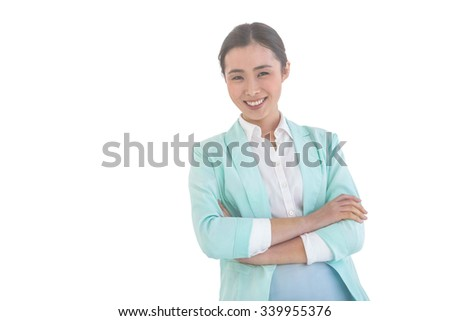 Smiling businesswoman with folded arms at the desk in work