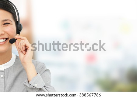 Smiling businesswoman with headset on against view of business stuffs on scale - stock photo