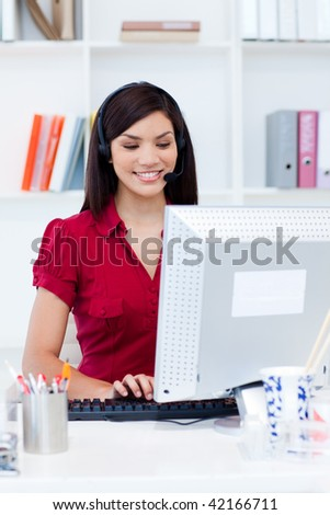 Smiling businesswoman with headset on at a computer in the office - stock photo