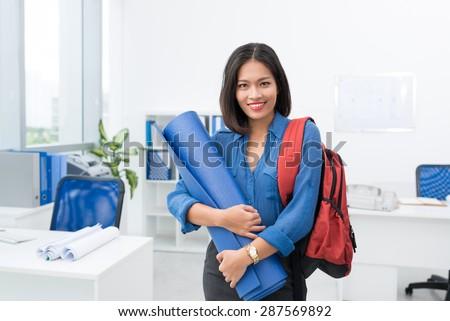 Smiling businesswoman with knapsack holding exercise mat - stock photo