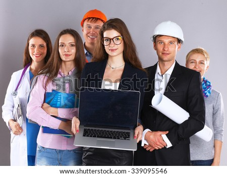 Smiling businesswoman with laptop  and group of industrial workers - stock photo