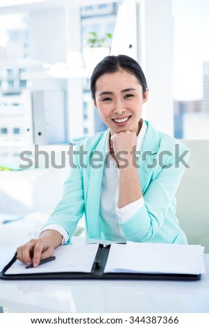 Smiling businesswoman with notes at desk in work