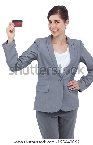 Smiling businesswoman with red credit card on white background