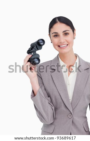 Smiling businesswoman with spy glasses against a white background - stock photo
