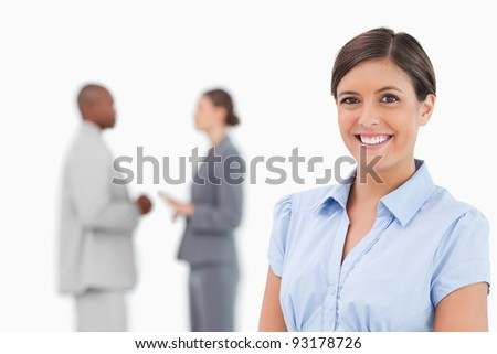 Smiling businesswoman with talking associates behind her against a white background