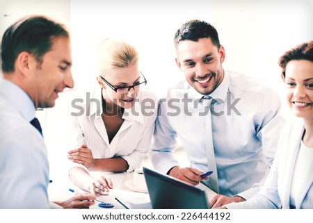 smiling businesswoman with team on meeting in office - stock photo