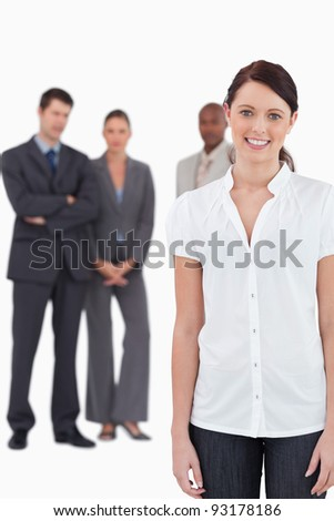 Smiling businesswoman with three co-workers behind her against a white background