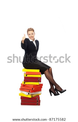 Smiling businesswoman with thumb up sitting on a stack of folders - stock photo