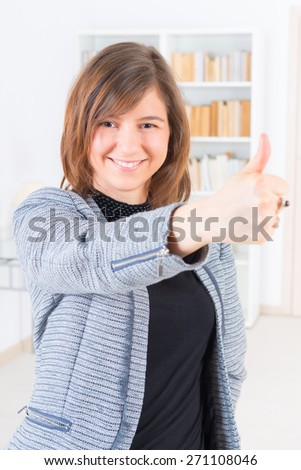Smiling businesswoman with thumbs up gesture - stock photo