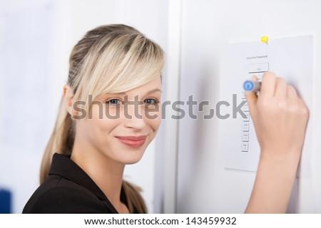 Smiling businesswoman writes something on the wall - stock photo