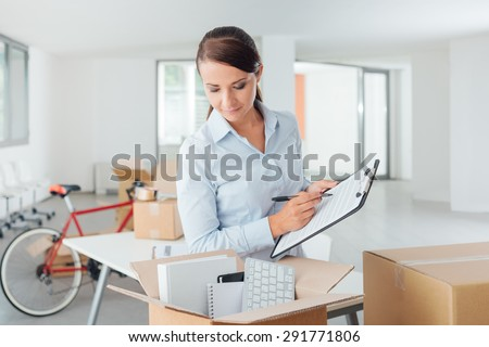 Smiling businesswoman writing a relocation checklist for her office on a clipboard and looking into an open carton box - stock photo